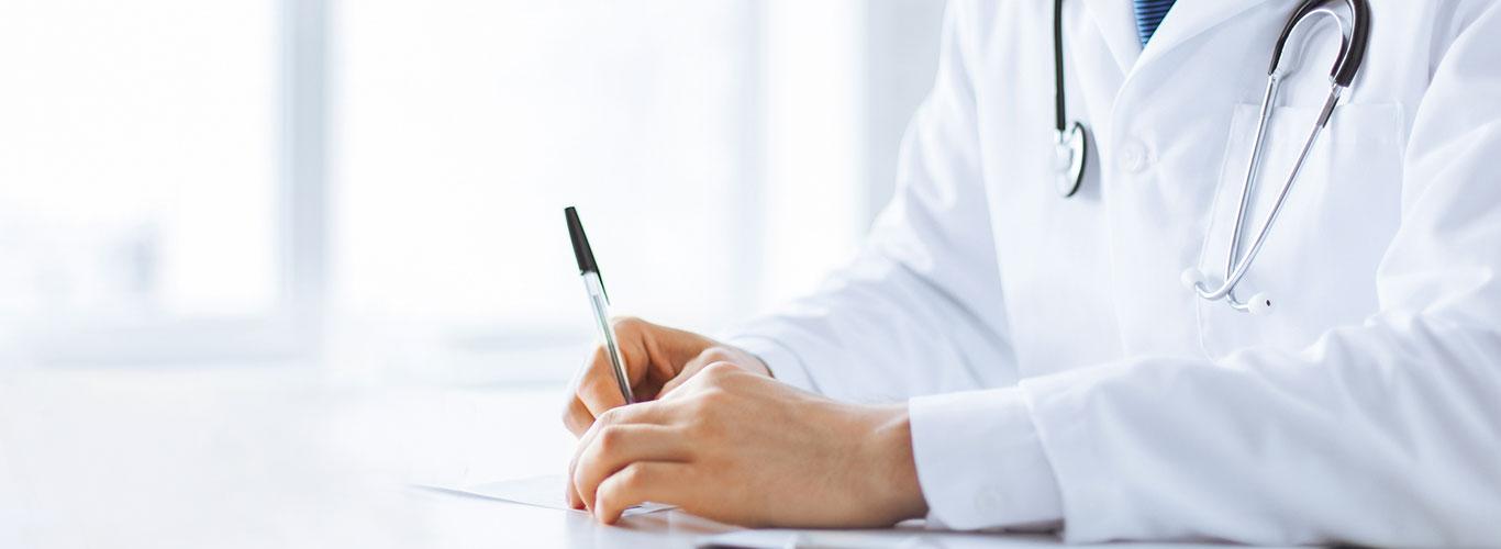 Lääkärin kädet. Lääkäri pitelee käsissään kynää.